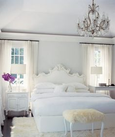 ::This white bedroom is Chic. Chic. Chic. I love how it is full of texture with a pop of color from the deep purple flowers. The chandelier keeps it ultra lux.::
