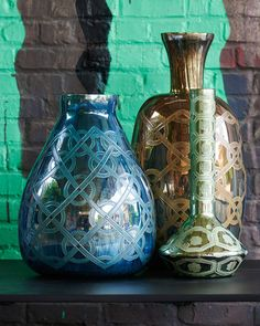 A stunning and unusual decorative vase in glass. With an elegant elongated teardrop form and long straight neck. The beautiful metallic pale lime finish features a striking hand-applied textured geometric decoration.