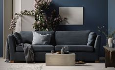 Deep grey, blue and neutral colours create this simple, yet stunning living room | the statement florals create a fresh summery backdrop and the ceramics, boxy sofa table and rustic bench add texture to the space | Seen here: an IKEA Stockholm sofa with a Bemz cover in Graphite Grey Simply Linen on an IKEA Stockholm sofa