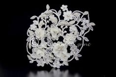 Rhinestone centered ivory organza and satin flowers accent this wired flower and vine lace wedding cap. A strand of wired ivory pearls defines the edge and more pearls and rhinestones dot the lace.Thi