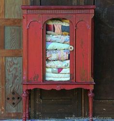 Vintage quilt collection displayed in painted red cabinet - Petticoat Junktion