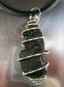 Tektite (Meteorite Impactite) & Silver Spiral Pendant    Contemporary, organic, rugged and exotic, this pendant is a raw tektite (meteorite impactite) drop that has been wrapped in silver-filled wire and suspended on black leather cord, which closes with a lobster-claw clasp. The tektite measures 39x15x16mm and the entire pendant is 52mm long, including the bail. It's unisex design makes it a great gift for both men and women.