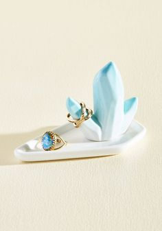 With beautiful baubles so treasured, you wouldn't dare jumble them on your dresser. This ceramic jewelry dish organizes your small accessories on its asymmetrical dish and blue-glazed gem. Truly a dream!