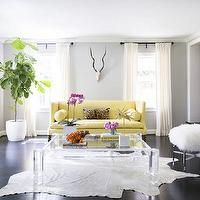 Domino Magazine - living rooms - yellow and gray living room, gray walls, living room with gray walls, off white curtains, yellow sofa, yellow couch, high back sofa, high back couch, high back yellow sofa, yellow bolster pillows, bolster pillows, cheetah pillow, cheetah lumbar pillow, lucite coffee table, white cowhide rug, dark wood floors, art over fireplace, fiddle leaf fig, fiddle leaf fig plant,