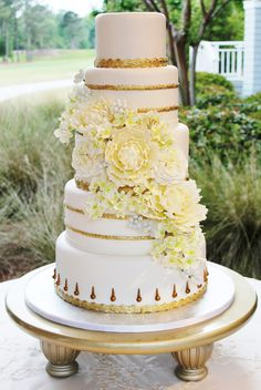 This ivory cake with gold accents is wrapped in a sugar flower cascade of creamy peonies, green hydrangea, white garden roses and pale blue berries.