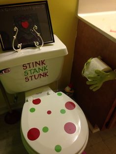 Grinch bathroom green gloves for grinch hands holding toilet paper. Stink stank stunk on toilet in vinyl
