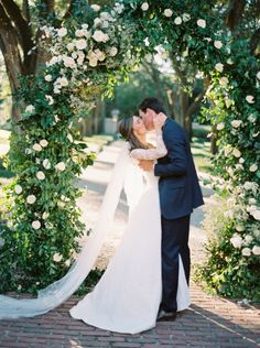 "The bride had always envisioned her wedding in an overgrown garden. ""I was inspired by the home in Great Expectations,"" says Hillary Hogan. ""Unfussy, natural floral arrangements; antique urns as vases; smilax-adorned French chandeliers; candelabras covered in vines; and outdoor garden furniture."""