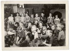 This is a great snapshot of school children during storytime - look at their faces, the teacher has their full attention. I wonder what story is being read...