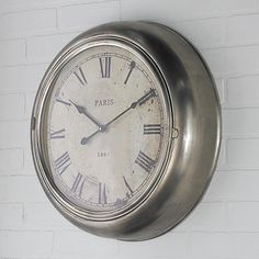 """20"""" Industrial Metal Clock Roman numerals add distinct style to this industrial wall clock. The rustic raw galvanized metal finish is tailored by the cream clock face and delicate hands for a functional design accent to any room. (19.5""""Hx19.5""""Wx4.5""""D)"""