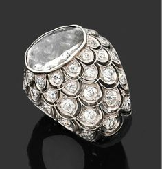 Platinum and diamond ring by Suzanne Belperron, featuring scales set with brilliant-cut diamonds surrounding an 18th century table-cut diamond, circa 1955.