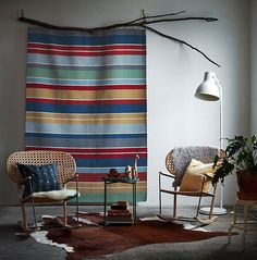 Fargerikt, stripete ullteppe som henger på veggen som dekorasjon.