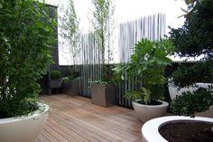 Sont utilisés des contenants évasés de différentes tailles. Ils évoquent les jardins en terrasse d'extrême Orient. Les bacs à arbustes sont en inox microbillé. Pour une cloison originale, on a pensé au brise-vue en tige de fibre de verre. Et aussi une fontaine pour renforcer le côté zen de cet espace.