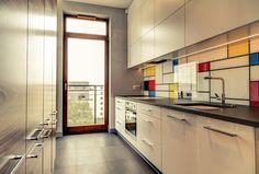 Nowoczesne wykończenie kuchni o układzie liniowym z elektrycznie otwieranymi szafkami, białą płyta indukcyjną i wpuszczonym w blat ceramicznym zlewem. Backsplash z reprodukcją obrazu Mondriana.