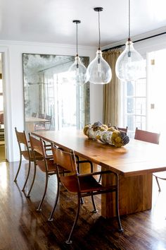Wood dining space with multiple glass chandeliers