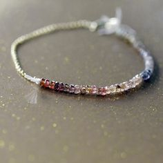 Sapphire Array Bracelet $79.00  A sweep of gorgeous Sapphire gems in a beautiful array of color creates a spectrum effect in sparkling stones. Strung on light pink silk cord with the ends left intentionally to fray, and juxtaposed with a 14k goldfill chain and lobster clasp.