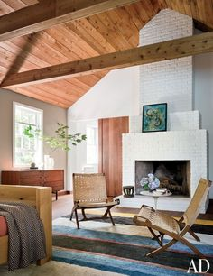 A painting by Mary Morez rests on the brick fireplace in the master bedroom; the chairs are '60s Hans J. Wegner designs from Laurin Copen Antiques.