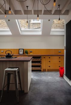 British-Standard-North London-Kitchen-Remodelista-03. Salvaged iroko school laboratory worktops from Retrouvius. India Yellow and Pointing by Farrow & Ball were used to create the two-tone paint scheme. Carrying the India Yellow above the work top creates a visual and graphic datum line across the working side of the kitchen.