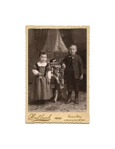 1895 cabinet card showing a cute little girl holding a tiny handbag and standing next to her older brother. On the small table between the two is a stereoviewer and a small stack of stereoviews.   Images showing photographic equipment and/or viewers such as this are very desirable in the vintage photo collecting world.  Photographed by Westbrook, Carson City Michigan.
