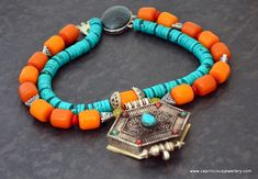 A Ghau box pendant on a necklace of faux beeswax amber and turquoise dyed magnesite by Caprilicious Jewellery
