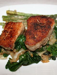 Tender garlic seared tuna is served on a bed of wilted spinach with sautéed garlic and onions.