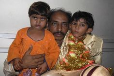 Seven-year-old groom Mohammad Waseem (right) sits with his four-year-old bride, Nisha, and his father, Mohammad Ismil, in a Karachi police station. Pakistani police raided a child marriage ceremony in 2008 and arrested a cleric who was presiding over the wedding. (Stringer/Reuters).