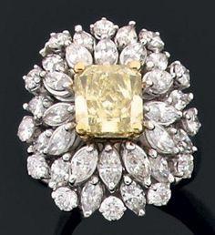 """Importante bague en or gris ornée d'un diamant jaune """"Fancy intense"""" de taille radiant dans un bel entourage de diamants navettes et brillants. Tour de doigt: 54 Diamant jaune accompagné d'un certificat… - Aguttes - 12/12/2012"""
