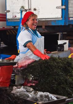 A fishmonger at Lima's Villa Maria fish market laughs with her clients about the days catch. The fish market is packed early each morning with vendors and buyers haggling over prices.(c) GTH & Nathan DePetris
