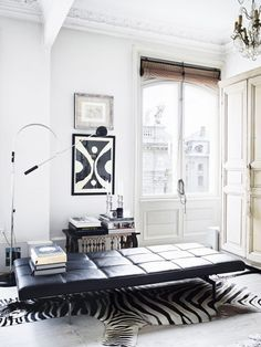 Bright living space with a black leather daybed and a faux zebra rug