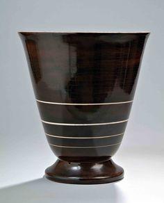 Jacques Adnet (1901-1984)  Vasque lumineuse en stuc sur large base, à couverte brune rythmée de cercles successifs incisés, patine crème. (un percement postérieur). haut. 40,5 cm - diam. 36,5 cm