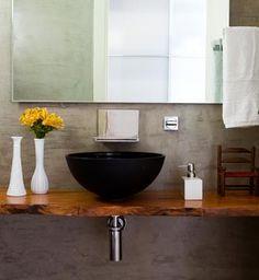 Manda cimentar! Este lavabo de 2m² recebeu no piso e nas paredes o revestimento de cimento queimado cinza. Com o mesmo conceito, a bancada da pia é de madeira maciça extraída de área de manejo sustentável, além da cuba de apoio de vidro negro e da bica cromada, da Punto. Vasos e saboneteira da Galeazzo Design.