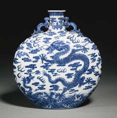 A RARE BLUE AND WHITE 'DRAGON' MOONFLASK QING DYNASTY, QIANLONG PERIOD, the flattened globular body rising from a short oval foot to a slender waisted neck, flanked by a pair of chilong handles, the front and back face painted with vivid shades of cobalt-blue depicting a five-clawed dragon and a smaller attendant dragon leaping from turbulent cresting waves, the base originally with a six-character seal mark which has since been erased  29.5cm., 11 5/8 in.