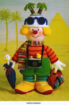 """From 'Knitted Clowns', Pt.1 of Jean Greenhowe's 'Red Nose Gang' collection meet the intrepid traveler Godfrey Gadabout. He is knitted with DK wool and stands 30cm/12"""" tall (excl. hat decor). He has all he needs to roam the globe and come home full of adventurer's tales. Designed and published by Jean Greenhowe Designs in 1992"""