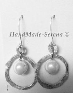 Orecchini realizzati con cerchi di filo di acciaio battuto e perla bianca al centro.