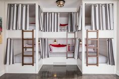 A unique touch is added to custom grommet bunk beds featuring white and gray pleated curtains matching bedding with red accent pillows.