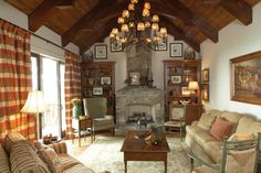 vaulted rustic living room with wooden beams in the ceiling, wooden flooring, white walls, stone fireplace, brown rug, brown sofa, wood table, chendelier of Beautiful Ideas on Airier and Brighter Vaulted Ceiling Living Room