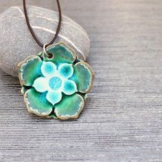 """ceramic pendant necklace.  Porcelain flower shaped pendant with layers of petals. Glazed in shades of green aqua and teal with a crackled glass middle. The bail is sterling silver and I've torch soldered it closed. A 18"""" leather cord with sterling clasps is included."""