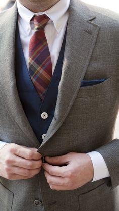 Plaid tie, contrasting vest.