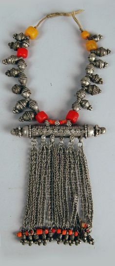 Yemen ~ Razih Silver necklace of plain bobbles (xaTrah/xaTaayir) and knobbed bobbles (zirri/zurarah) and red and yellow beads, with amulet-case (Harz) with chains and orange beads pendant from it. 20th century, acquired by the British Museum in 1993.