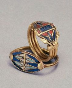 2 gold rings with symbolised flowers from the 18th dynasty (1400-1200BC) that are in The Walters Art museum in Baltimore. The ring on the right with the red Carnelian and Lapiz Lazuli even has small buds of the flower in gold. The ring left with the delicate granulation rim uses light and dark blue glass. The white is also glass with small purple speckles. Both are made in the typical Egyptian cloison style.