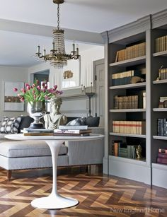 Contemporary classic formal sitting room. Loving the bookshelves and chevron wood flooring.