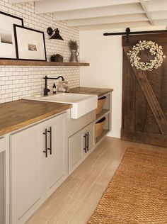 gray cabinets, farm sink, subway tile, sconce, cotton wreath on barn door, sisal rug, floor tiles