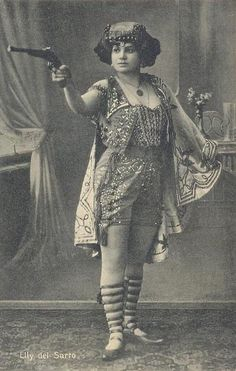 Elly del Sarto was a sideshow trick shooter of the early 1900s. She also played instruments and was an all-around performer.