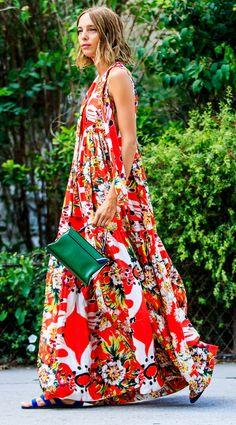 Une robe longue rouge et blanche aux motifs ethniques, des sandales bleu foncé en velours et une pochette verte.