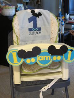 Mickey 1st Birthday bib and high chair decoration - I made the high chair decoration from scrapbook paper, laminated with contact paper, and attached with tape.