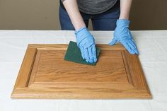 Wearing your latex gloves, apply a generous amount of deglosser onto the scrub pad provided in the kit, and thoroughly wipe each cabinet door