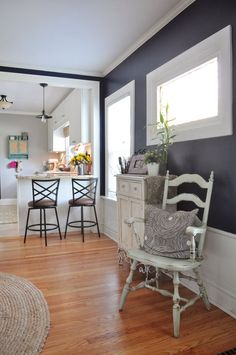 vintage whitewashed chair in room with warm wood floors and dark walls with white wainscoting