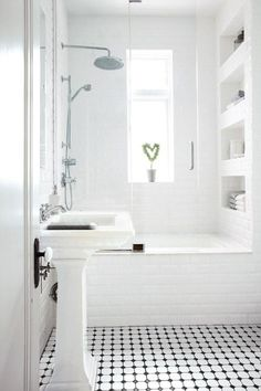 petite salle de bains blanche avec une baignoire-douche, niche murale et carrelage de sol en noir et blanc