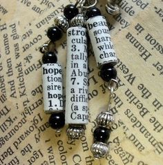 "recycled/rescued/upstyled book page rolled into tube to create beads...  DIY Rolled Paper Beads (No Tutorial - simply glue/cut paper and roll - you may want to roll around a wax paper covered pencil, etc.) each tube has a word and it's definition. This earring showcases""faith, humor and strength."""