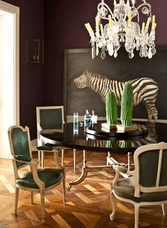 Round dining table with a variety of green upholstered chairs, crystal chandelier, and zebra painting