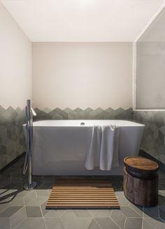 Mutina's texturalTex by Raw Edgestiles enclose an Edge Bathtub from Victoria & Albert with an Axor Starck Freestanding Tub Filler.